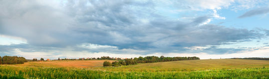 Countryside landscape panorama with green field. And small village Royalty Free Stock Photos