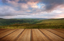 Countryside landscape panorama image across to mountains with wo. Beautiful landscape panorama across countryside to mountains with wooden planks floor Stock Image