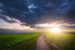 Countryside landscape path leading through fields towards dramat Royalty Free Stock Photos