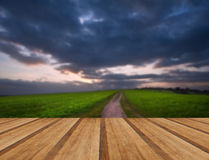 Countryside landscape path leading through fields towards dramat Stock Photos