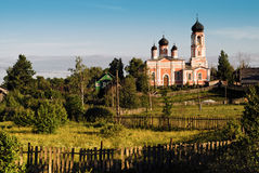 Countryside landscape with temple. Rural church with fence around field , Russia Stock Photos