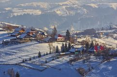 Winter countryside landscape. Countryside landscape with traditional Romanian village in the valleys of Bucegi mountains on a sunny cold winter morning in Royalty Free Stock Images