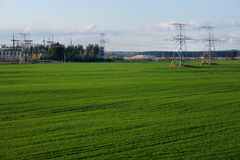 Countryside lanscape with power lines. Countryside landscape with power lines and lush green grass field Royalty Free Stock Photo