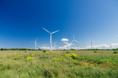 Countryside meadow with wind turbines generating electricity. Green energy concept stock photography