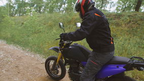 The countryside. Motorcyclist goes into full gear to his motorcycle. stock footage