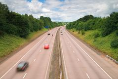 Countryside Motorway. Motorway cutting through the rural countryside - motion blue to vehicles royalty free stock image