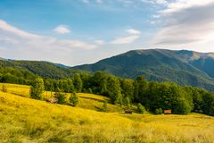 Countryside in mountains. Beautiful landscape with grassy alpine hills. abandoned woodshed and hay barrack on the meadow. mountain ridge in the distance stock photography