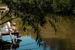 The countryside nature, trees and lake in the green colors. Father and son sitting on a wooden bridge and waiting for a stock images