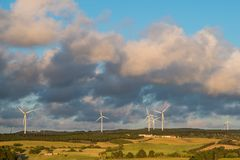 Countryside of old farms and fields contrasted with modern wind turbines under a beautiful sky with puffy clouds at sunset royalty free stock photos