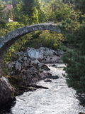 Countryside old packhorse stone scottish bridge. Over picturesque river in warm and sunny summer day: CARRBRIDGE, SCOTLAND / GREAT BRITAIN UK – AUGUST 2016 Royalty Free Stock Images