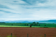 Countryside panorama in Scotland. Panoramic view of fields and farmhouses with Scottish Highlands in the background Royalty Free Stock Image