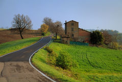 Countryside in Parma, Italy. Beautiful lush, green countryside in Parma, Italy. Road winding along cultivated lands and old house in the background royalty free stock photos