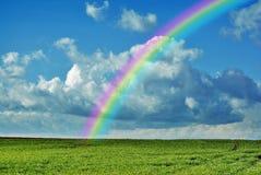 Countryside rainbow. A rainbow arches through a cloudy blue sky over green farmland royalty free stock photography