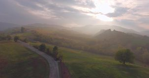 Countryside Road Aerial View. Breathtaking aerial drone footage: Flight over autumn trees, meadows in sunset soft light and haze. Majestic landscape, flying over stock footage