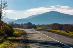 Countryside road in autumnal mountainous area. Beautiful view of high mountain in the distance in fine forenoon weather Royalty Free Stock Photos