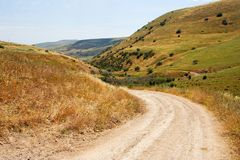 Countryside road bends among yellow hills Royalty Free Stock Photography