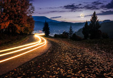 Countryside road with car lights at night. Countryside road with car lights. beautiful autumn mountain landscape at night in full moon light royalty free stock photo
