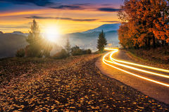 Countryside road with car lights at sunset. Countryside road with car lights. beautiful autumn mountain landscape at sunset Royalty Free Stock Photo