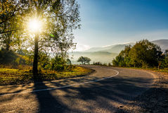 Countryside road down to the valley at sunrise. Beautiful bright weather in early autumn Royalty Free Stock Photo