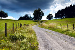 Countryside road with fence. Ground road in countryside with wooden fence Royalty Free Stock Images