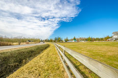 Countryside road with a fence. Horses, hay, and cars against blue cloudy sky Royalty Free Stock Photography