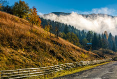 Countryside road and fence at the mountain foot. Cloud rising up from the forest at autumn morning Royalty Free Stock Photos
