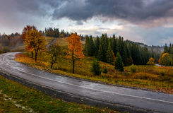 Countryside road through forest in stormy weather. Colorful dramatic sky and some fog over the hills Stock Photo