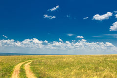 Countryside road, green grass and blue sky Royalty Free Stock Photos