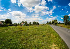 Countryside road with nice clouds. Countryside road at Ipolytolgyes, Hungary with nice clouds and a little house on the side. Picture taken with 8 mm fisheye Royalty Free Stock Image