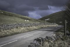 Countryside road in Peak District National Park,Derbyshire,Uk. Beautiful scenery,green hills and dramatic cloudy sky before thunderstorm.Rural road in scenic Royalty Free Stock Photo