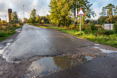 Countryside road. Rut with puddles. Road sign. The image of countryside road. Rut with puddles. Road sign stock photo