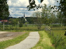 Countryside road. A small and narrow road in the swedish countryside with Lindesbergs church in the background Stock Image