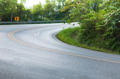 Countryside road with trees on both sides. Curve of the road to mountain stock photography