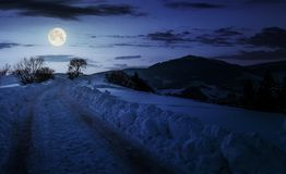 Countryside road uphill in snow at night. In full moon light. beautiful winter scenery in mountainous area Stock Images