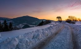 Countryside road uphill in snow at sunset. Beautiful winter scenery in mountainous area Stock Image