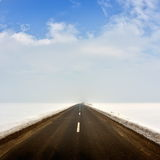 Countryside road through winter field Royalty Free Stock Photos