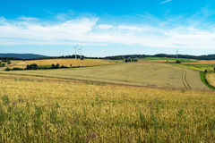 Countryside scenery with yellow and green wheat fields, hills and wind energy generator turbines royalty free stock photos