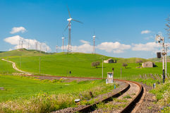 Countryside in Sicily. Railway running across the hills in the sicilian countryside with wind turbines in the background Stock Photos