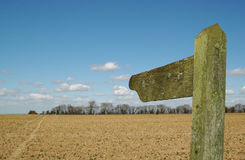 Countryside signpost. Empty signpost through field in the direction of a single track Royalty Free Stock Photos