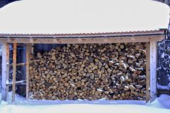 Winter, snow-covered stack of firewood under a snow-covered roof, Bavaria, Germany stock image