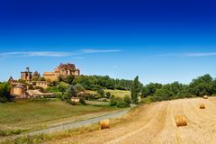 Countryside summer landscape of Biron, France. Countryside summer landscape with hay bales on the field and Chateau de Biron on the hilltop in the background stock image
