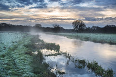 Countryside sunrise landscape with moody sky and flowing river Stock Images