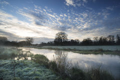 Countryside sunrise landscape with moody sky and flowing river Stock Photography