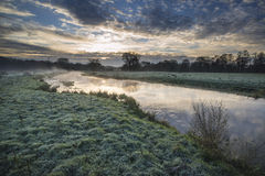 Countryside sunrise landscape with moody sky and flowing river Royalty Free Stock Photo