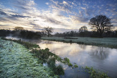 Countryside sunrise landscape with moody sky and flowing river Royalty Free Stock Photos