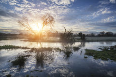 Countryside sunrise landscape with moody sky and flowing river Stock Photo