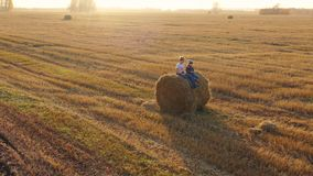 The kids sit on the haystack. They play and laugh.Countryside. Sunset stock video