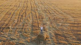 A teenager stands on a haystack and waves his hands. Outdoor entertainment. Countryside. Sunset stock footage