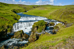 Countryside with trail near famous Skogafoss Waterfall, Iceland. On sunny summer day and blue sky Royalty Free Stock Images