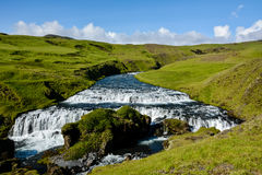 Countryside with trail near famous Skogafoss Waterfall, Iceland. On sunny summer day and blue sky Royalty Free Stock Photography